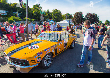 Vintage race cars parked in downtown Watkins Glen during the annual Vintage Race weekend Festival with spectators - Stock Photo