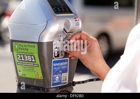 Closeup of woman feeding parking meter - USA - Stock Photo