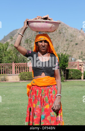 Woman carrying a big bowl filled rubble from a building site on her head, Jaipur, Rajasthan,India, - Stock Photo