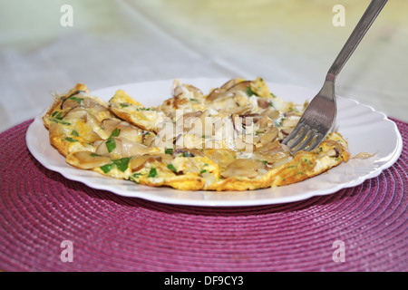 Scrambled eggs with mushrooms boletus on the plate - Stock Photo