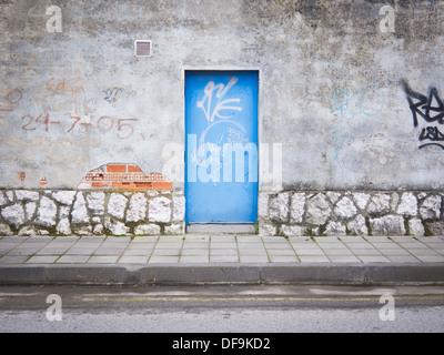 Santander, Spain: Lonely blue metal door in industrial estate - Stock Photo
