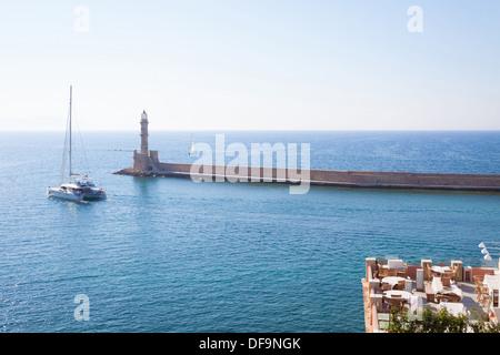 Chania, Greece: A catamaran leaves the old Venetian harbor of Chania in Crete Island. - Stock Photo