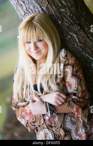 Young woman is smiling in the park - Stock Photo