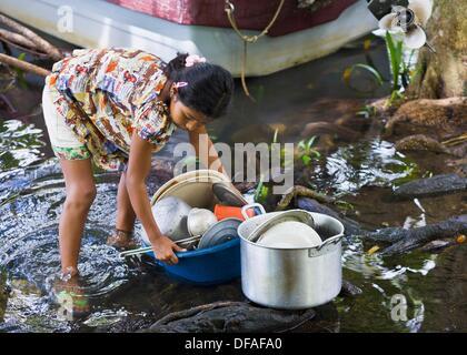 Guatemala, Rio Dulce, girl washing dishes in River - Stock Photo