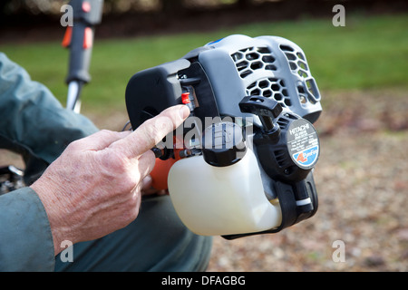 A man shows the petrol engine of a strimmer UK - Stock Photo