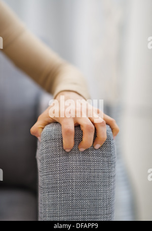 Closeup on hand of stressed woman sitting on sofa - Stock Photo