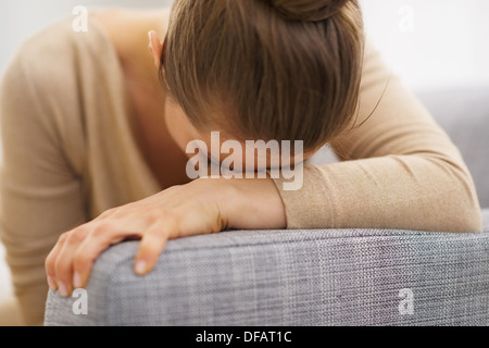 Frustrated young housewife sitting on sofa - Stock Photo