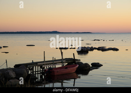 Rowing boat by an old pier at a summer evening. From the island Oland in Sweden. - Stock Photo