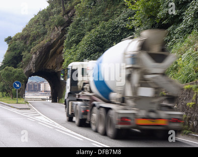Mixer truck about to go through small tunnel in the rock on a road by the beach - Stock Photo