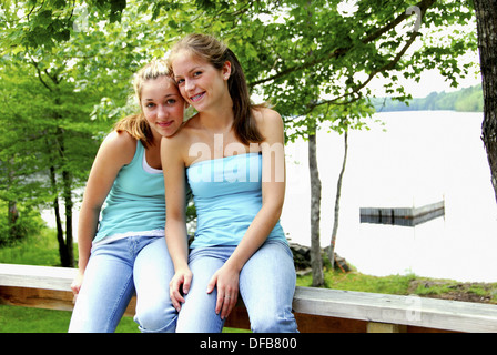 two teenage girls sitting together on railing at the cottage - Stock Photo