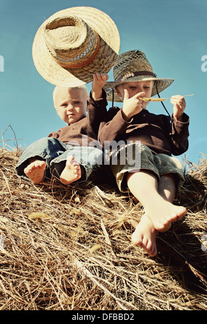 Two young children, a little boy and his baby brother are sitting on a hay bale, wearing straw hats, in front of - Stock Photo