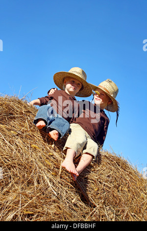Two happy young children, a boy and his baby brother, are sitting on a hay bale in a field on a farm, wearing straw - Stock Photo