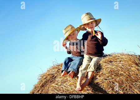 Two children, a young boy and his baby brother are sitting outside on hay bales, wearing straw hats on a sunny Autumn - Stock Photo