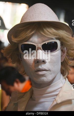 street mime posing at the Silom Street Fair in Bangkok Thailand - Stock Photo