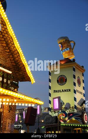 Paulaner beer tower at the Oktoberfest in Munich in the twilight - Stock Photo