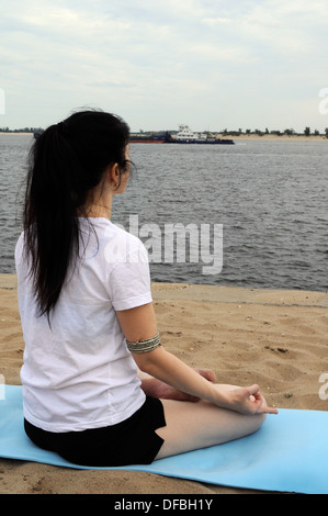 Woman sitting in lotus position on a river bank, half back view - Stock Photo