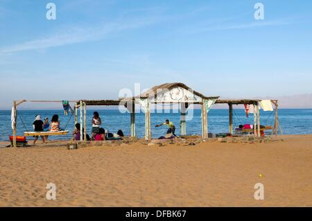 tourists playing on the beach next to the Red Sea in the Sinai Desert of Egypt - Stock Photo