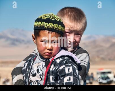 portrait of two Kazakh boys in the Altai Region of Bayan-Ölgii in Western Mongolia - Stock Photo