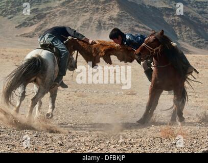 Kazakhs playing kokbar, a traditional sport in which tug of war over a fox or goat pelt is played on horseback, - Stock Photo