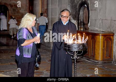 A believer talks to a priest before visiting the most important site of the Church of the Holy Sepulchre, the Aedicule - Stock Photo