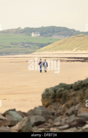A couple holding hands in love walking along a deserted beach at Newborough on Anglesy with sand dunes in the back - Stock Photo
