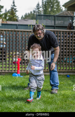 Cute action of model released grandson laughing,playing, having fun and being chased by Grandpa, in the back yard. - Stock Photo