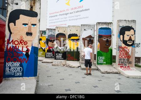 sections of original Berlin Wall painted with world leaders at Checkpoint Charlie in Berlin Germany - Stock Photo