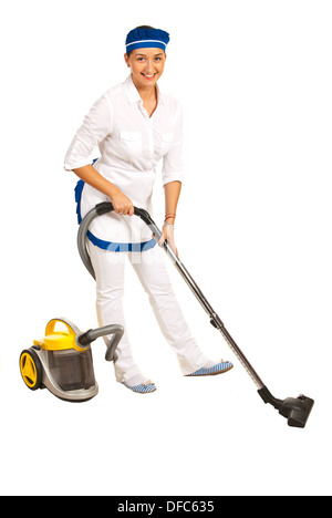 Maid in uniform using vacuum cleaner to clean the room against white background - Stock Photo
