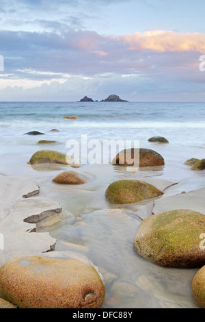 Tones of sunrise begin to fill the sky on a summers day at Porth Nanven in Cornwall - Stock Photo