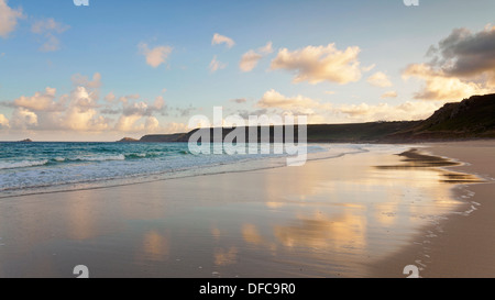 Start of a summers day on Sennen beach in Whitesand Bay near Lands End Cornwall, clouds reflected in the wet sand - Stock Photo