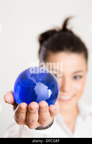 Young woman holding model of world in hand, close up - Stock Photo