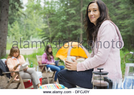 Portrait of woman with coffee mug sitting on table at campsite - Stock Photo