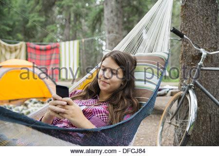 Teenage girl using smart phone in hammock - Stock Photo