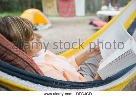 Relaxed senior woman reading book in hammock at campsite - Stock Photo