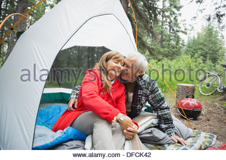 Romantic senior couple sitting in tent at campsite - Stock Photo