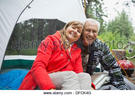 Portrait of happy senior couple sitting in tent at campsite - Stock Photo