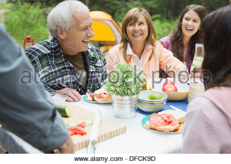 Happy senior couple enjoying meal with family at campsite - Stock Photo