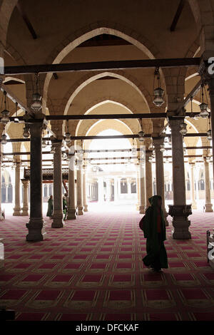 silhuoette of woman walk on carpets at Mosque of Amr Ibn Al-as in old Cairo - Stock Photo