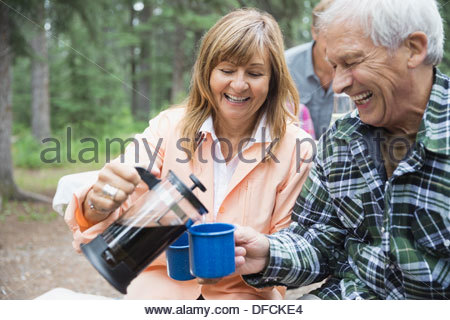 Senior woman serving black coffee to man at campsite - Stock Photo