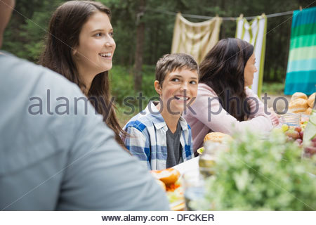 Cheerful boy having food with family at campsite - Stock Photo