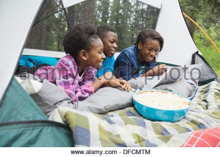 Siblings looking at digital tablet in tent at campsite - Stock Photo