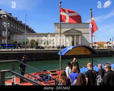 Tourists' canal cruise boat by Christiansborg Palace on Slotsholmen or Castle Isle in Copenhagen, Zealand, Denmark, Scandinavia