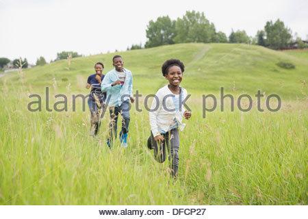 Cheerful siblings running through field - Stock Photo