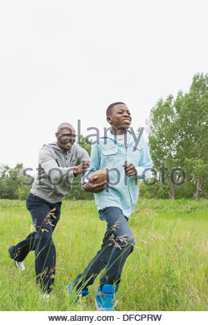 Father and son playing American football outdoors - Stock Photo
