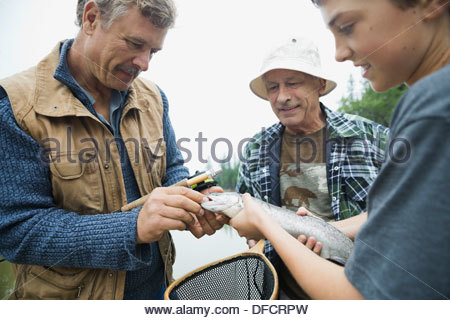 Male family members removing hook from fish - Stock Photo