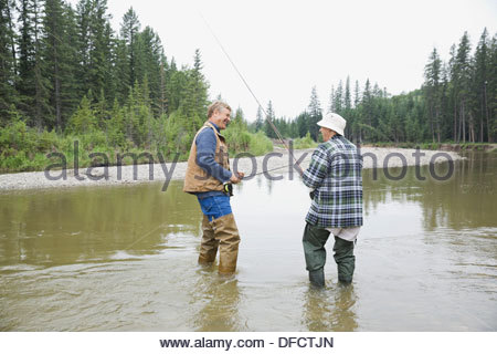 Father and son with fishing rods standing in river - Stock Photo