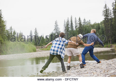 Male family members skipping rocks on a river - Stock Photo