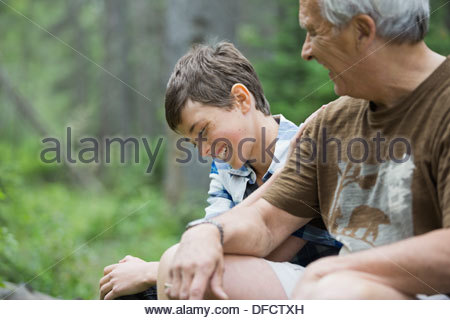 Happy boy sitting with grandfather in forest - Stock Photo