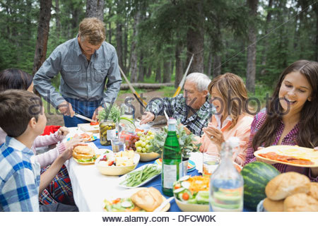 Happy multi-generation family enjoying meal at campsite - Stock Photo