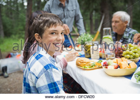 Portrait of boy having meal with family at campsite - Stock Photo